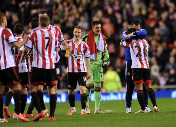 RELIEF: Gustavo Poyet and his Sunderland players celebrate saving their Premier League status