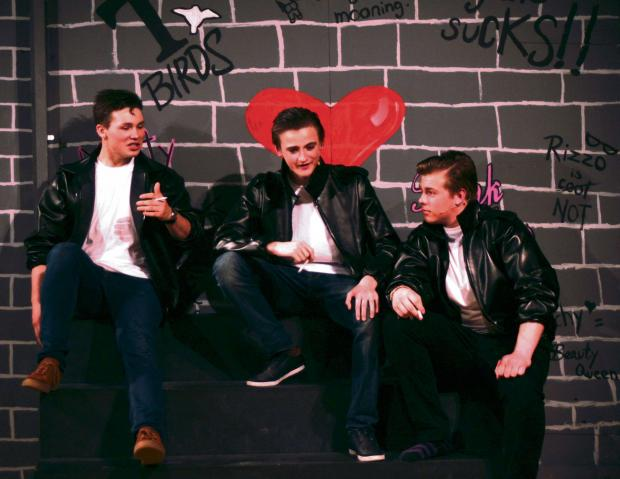 Cast members, from left to right, Jamie Preston, Sam Theakston and Chris Harrison during the performance of Grease.