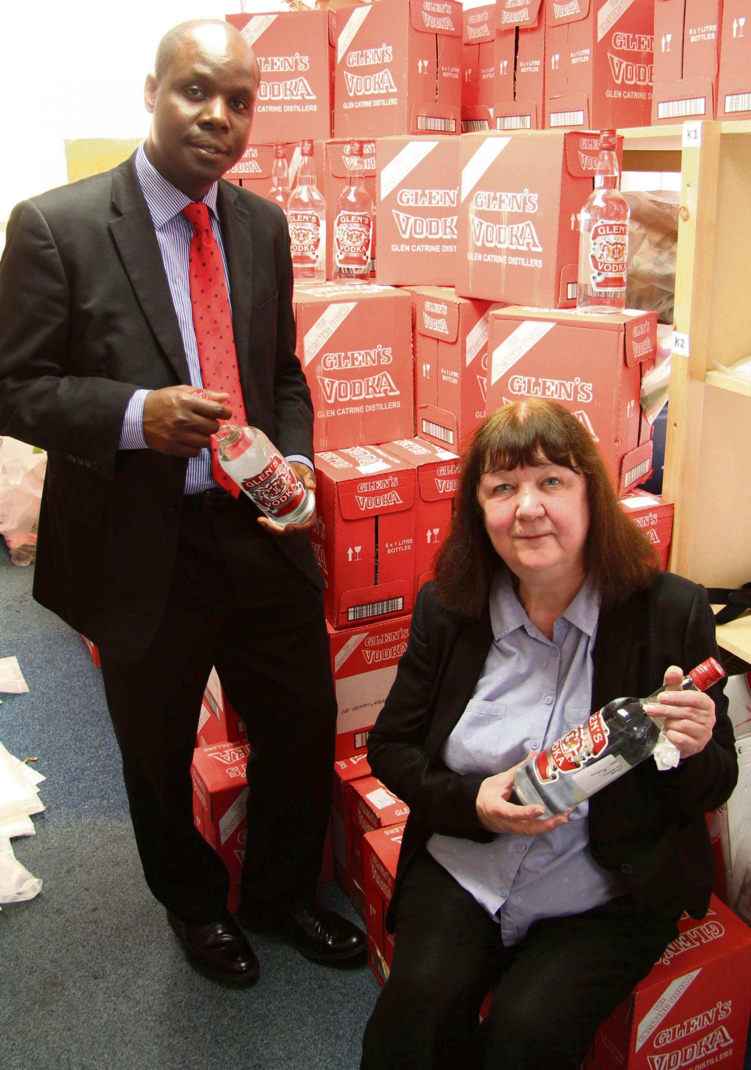 Edward Kunonga, Middlesbrough Council's director of public health with Councillor Julia Rostron with the mountain of seized counterfeit vodka.