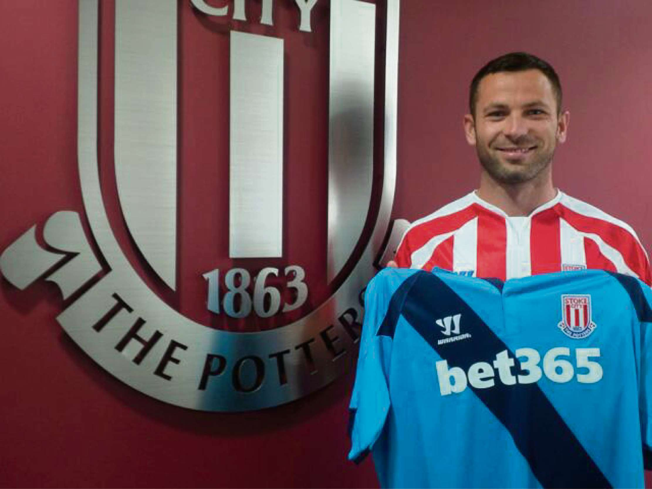 NEW BOY: Phil Bardsley holds the Stoke City shirt aloft after signing for the Potters from Sunderland yesterday