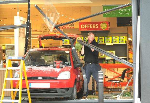 The Northern Echo: A workman attempts to remove some of the framework of the window at Waitrose in York after a driver accidently reversed her car through it. Picture: Garry Atkinson