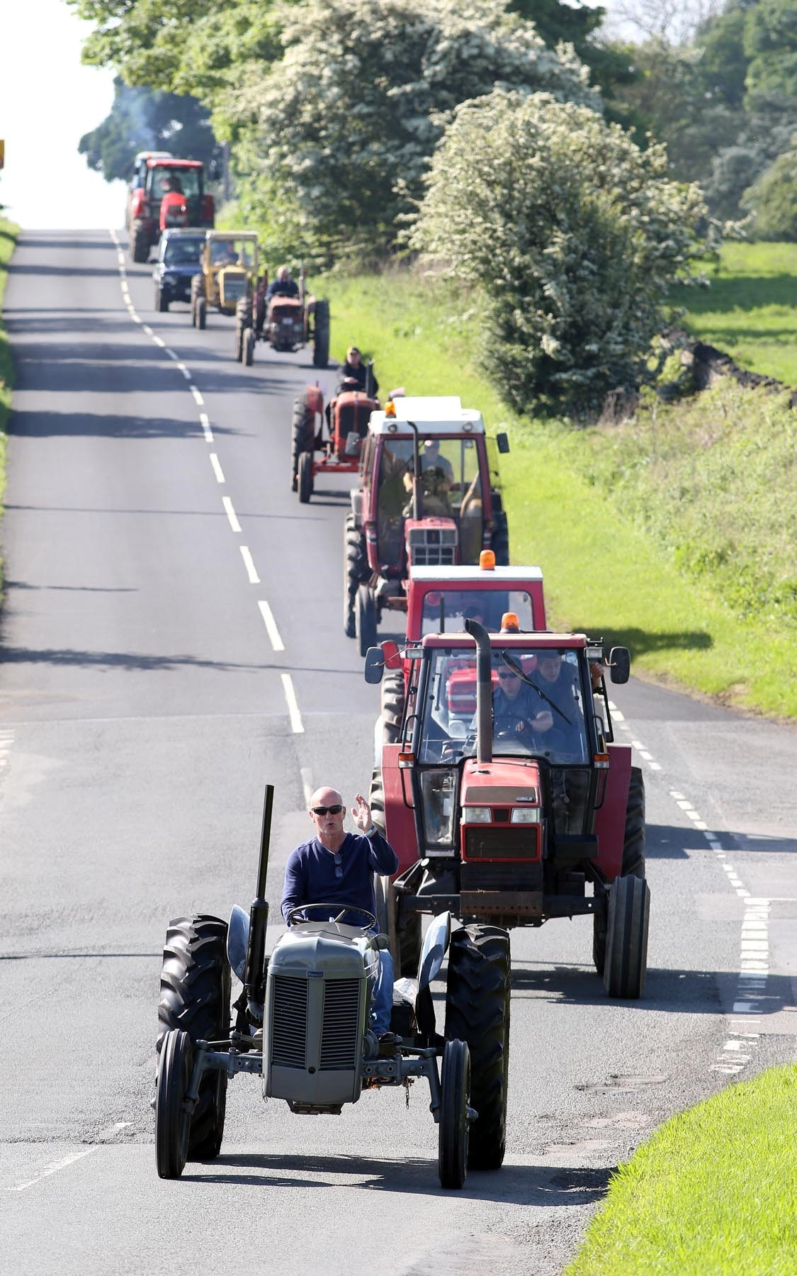 Tractors convoy through countryside during charity ride