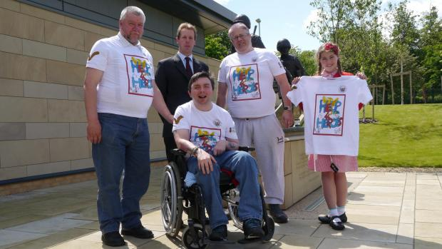 WINNING T-SHIRT: Lily Nicholson-Hume, 10, with veterans from left: Fred Bates, Martin Edwards and Andy Lake; and Tom Orde-Powlett, whose family owns Bolton Castle, at Phoenix House, Catterick Garrison.