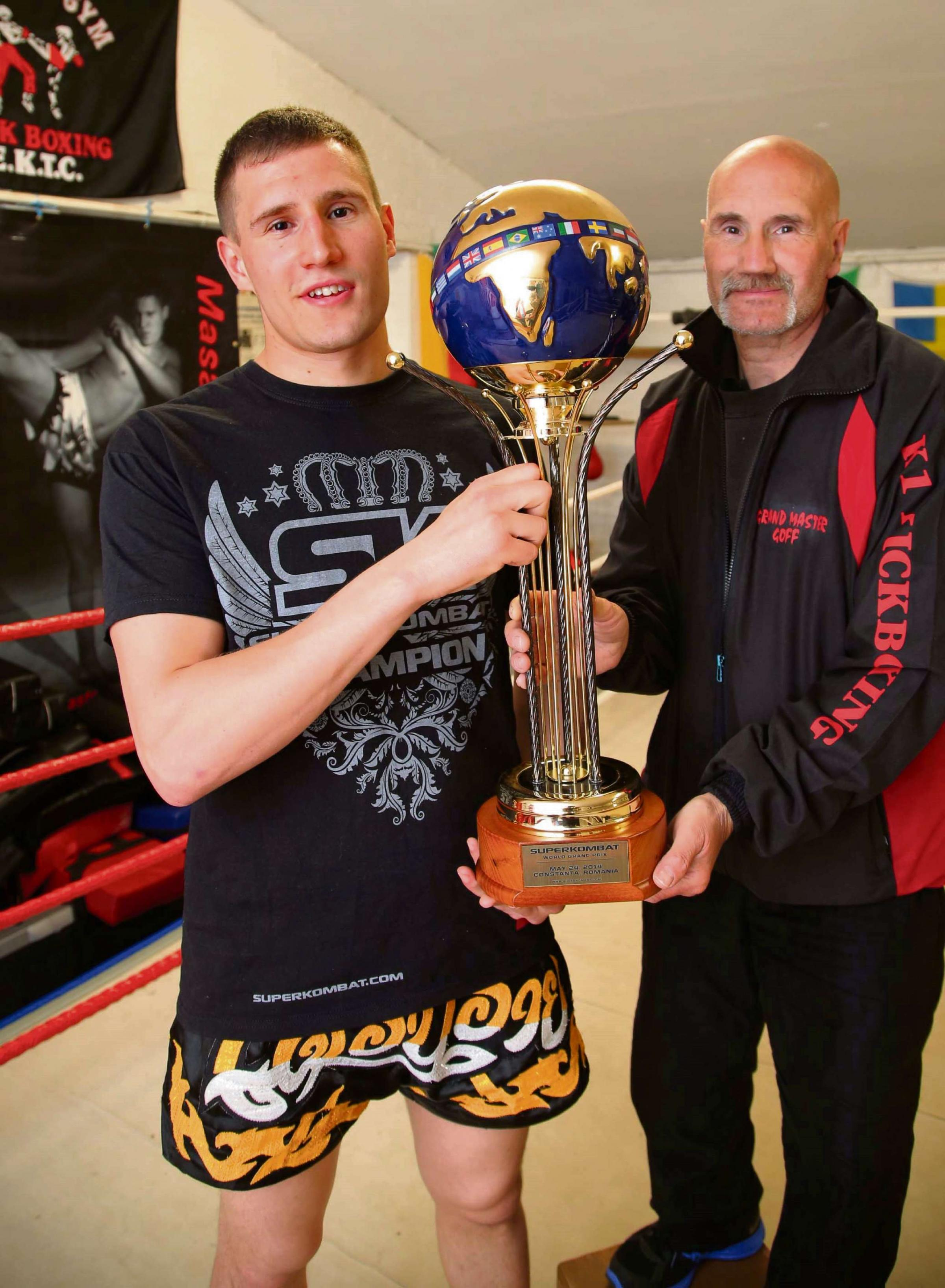 WORLD CHAMP: Jamie Bates with his trophy and, right, father Goff Bates pictured at the gym in Annfield Plain Picture: ANDY LAMB