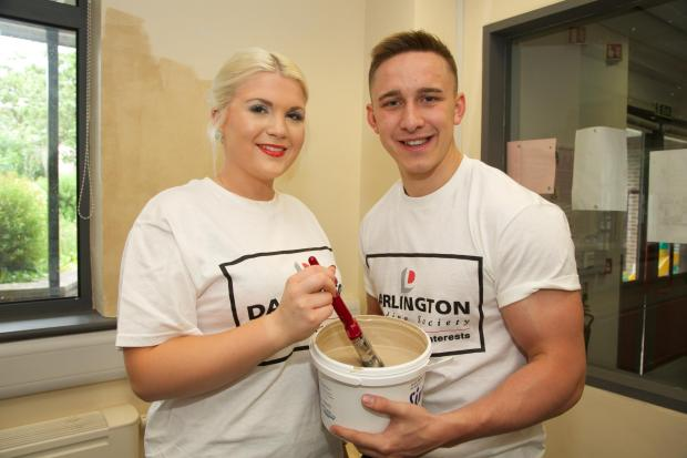 LEND A HAND: Josh Palin and Ellie Durham of Darlington Building Society volunteer to decorate the Red Hall Community Centre   Picture: Keith Taylor