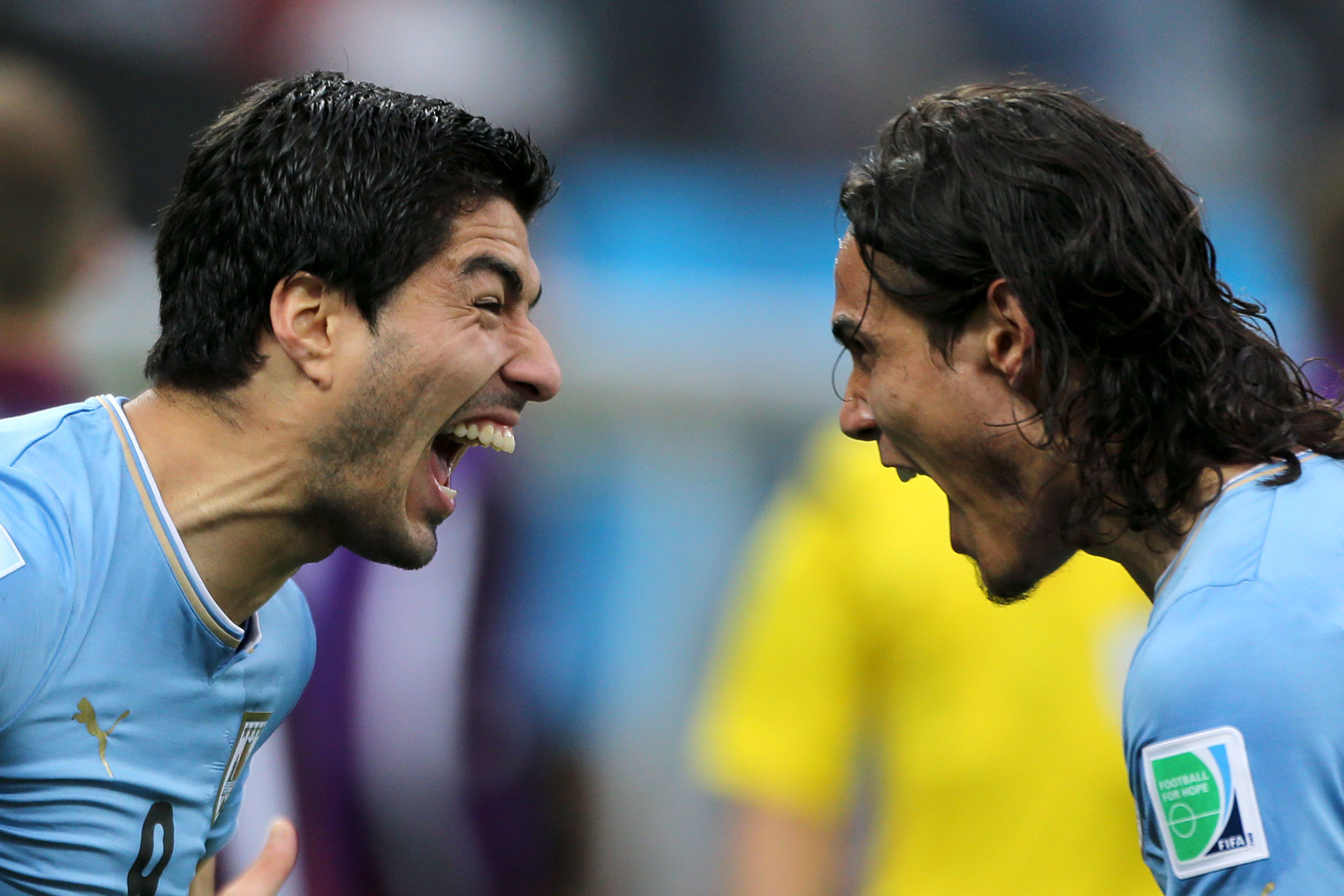 AT THE DOUBLE: Uruguay's Luis Suarez, left, celebrates scoring the first of his two goals in last night's win over England with strike-partner Edinson Cavani