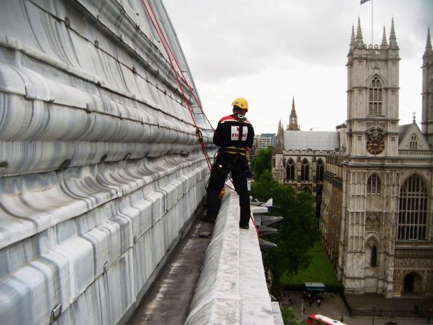 Paul Tinkler from STS working on the roof of Westminster Central Hall with Westminster Abbey in the background.
