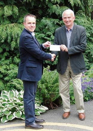 CHARITY FUNDS:Major Barney Barnbrook, left, receives a cheque from Peter Bickley, from John Weymes Racing.