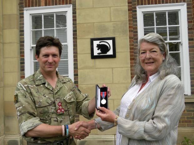 LOYAL SERVICE: Brigadier Charlie Herbert presenting the Imperial Service Medal to Elizabeth House outside Baden-Powell House, the headquarters of 4 Mechanized Brigade.