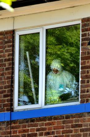 POLICE HUNT: A forensics officer examines a first floor room at The Acomb pub, York
