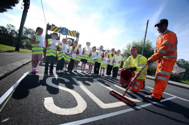 Class One pupils with road marking operatives Mathew Toothill (kneeling)  and Terry Fox, of contractors Coupe Line (8617914)