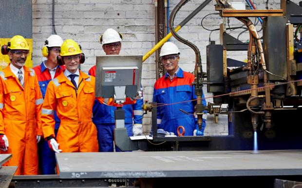 Jan Willem Verkaik, project director from Shell (third left), presses the button to make the first cut of steel at OGN Group on the Nyhamna project