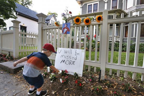 AJ Polis leaves a flower alongside a placard and a photo of the late actor Robin Williams as Mork from Ork, as people pay their respects at the home where the 80's TV series