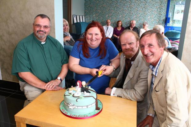 OPEN DAY: Keith Munt and Jenny Uzzell (centre) cut the celebration cake at Saint and Forster's open day, watched by the Rev George Callander (left) and Charles Cowling, author of the Good Funeral Guide.