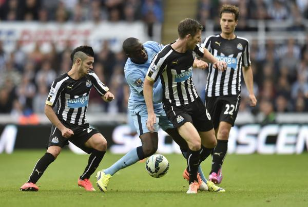 Thwarted: Yaya Toure is stopped by Remy Cabella and Mike Williamson