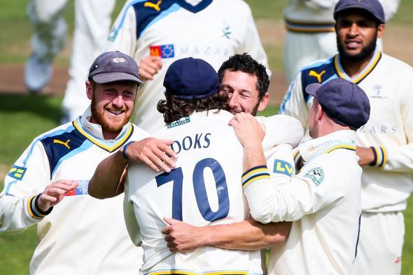 YORKSHIRE DELIGHT: Tim Bresnan is mobbed by his team-mates after taking the wicket of Sussex's Luke Wright at Scarborough yesterday – victory leaves the Tykes in command at the top of the County Championship