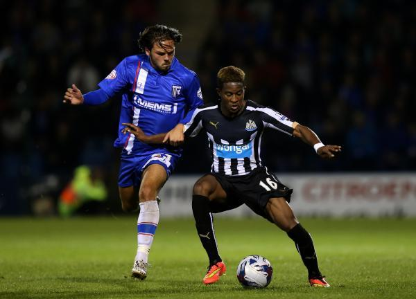 Newcastle United's Rolando Aarons, (right) battles for the ball with Gillingham's Bradley Dack, (left)