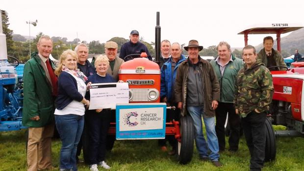 PLOUGHING ON: Pam Ashmore (second from left) and Sue Birdsall (third from left) from the Teesdale branch of Cancer Research UK are presented with a cheque from a group of Swaledale farmers who staged two tractor runs over summer