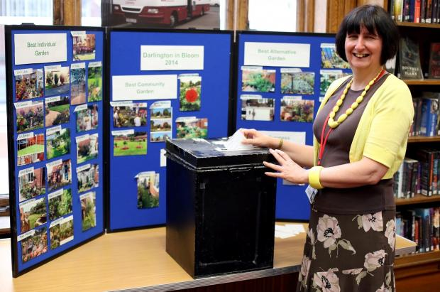 THE VOTES ARE IN: Darlington in Bloom votes can be cast in Crown Street Library as well as through Facebook.  Senior library officer Vicky Emmerson pictured with ballot box and pictures of the entrants  Picture: CHRIS BOOTH