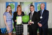 GREEN APPLE: Model Amy Dexter presented the award to CES director Karen Hindhaugh. Pictured with Cllr David Rose and Hugh Lang, chief executive of CES.