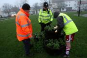 PAYING BACK:PC Keith Todd and Stephen Young watch the youngster plant flowersPicture:TOM BANKS