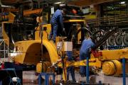 PRODUCTION LINE: Workers tend to parts on a Caterpillar truck	Picture: DAVID WOOD (17397291)