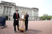 ARRIVAL: Footman George Oates (left) places an easel in the forecourt of Buckingham Palace in London to announce the birth of a baby girl. PICUTRE: Steve Parsons/PA Wire