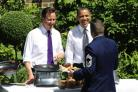 Prime Minister David Cameron (left) and US President Barack Obama serving food to a member of the military during a barbecue in the garden of 10 Downing Street, London. Picture: Matt Dunham/PA Wire