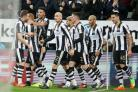 Newcastle players celebrate after an own goal by Aston Villa's Henri Lansbury