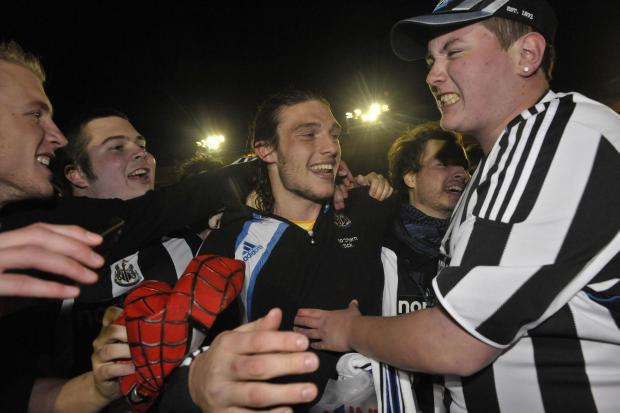 The Northern Echo: GLORY: Newcastle's Andy Carroll is swamped by Newcastle United fans as they invade the pitch to celebrate their side winning the Championship at Home Park in 2010