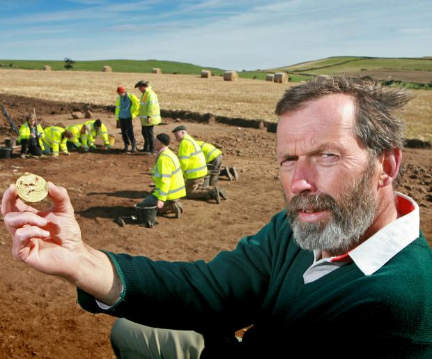 Archaeologist Steve Sherlock holds a gold Saxon bracteate, unearthed in fields on the coast, near Loftus.