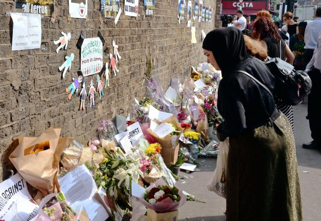 A woman leaves a floral tribute close to Finsbury Park Mosque in north London. Picture: John Stillwell/PA Wire