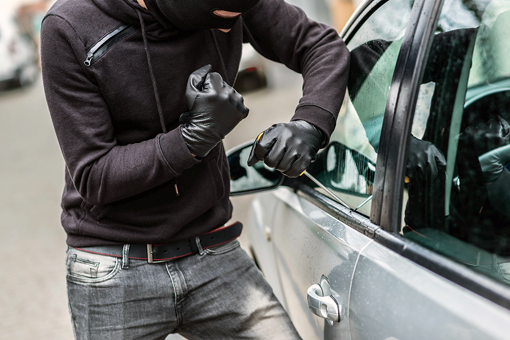 The man dressed in black with a balaclava on his head trying to break into the car. He uses a screwdriver. Car thief, car theft concept.