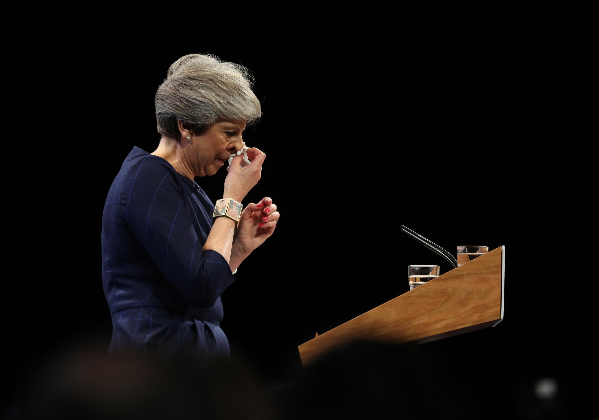 Prime Minister Theresa May wipes her nose as she delivers her keynote speech at the Conservative Party Conference. Picture: Owen Humphreys / PA Wire