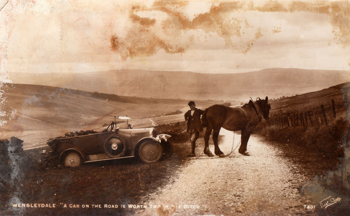 "The Northern Echo: WENSLEYDALE: This one is a gem. The rueful wording at the bottom says ""a car on the road is worth two in a ditch"". Can anyone tell us the type of car; can anyone tell us where in Wensleydale this was taken?"
