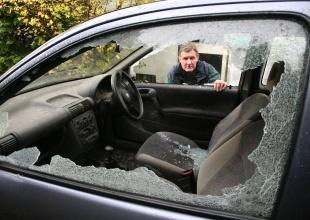 'TARGETED': John Gill views damage to his car