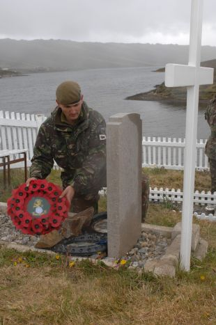 Major Andrew Roe, Officer Commanding, C Company 2nd Battalion The Yorkshire Regiment (Green Howards), laying a wreathe at the grave of Capt Hamilton