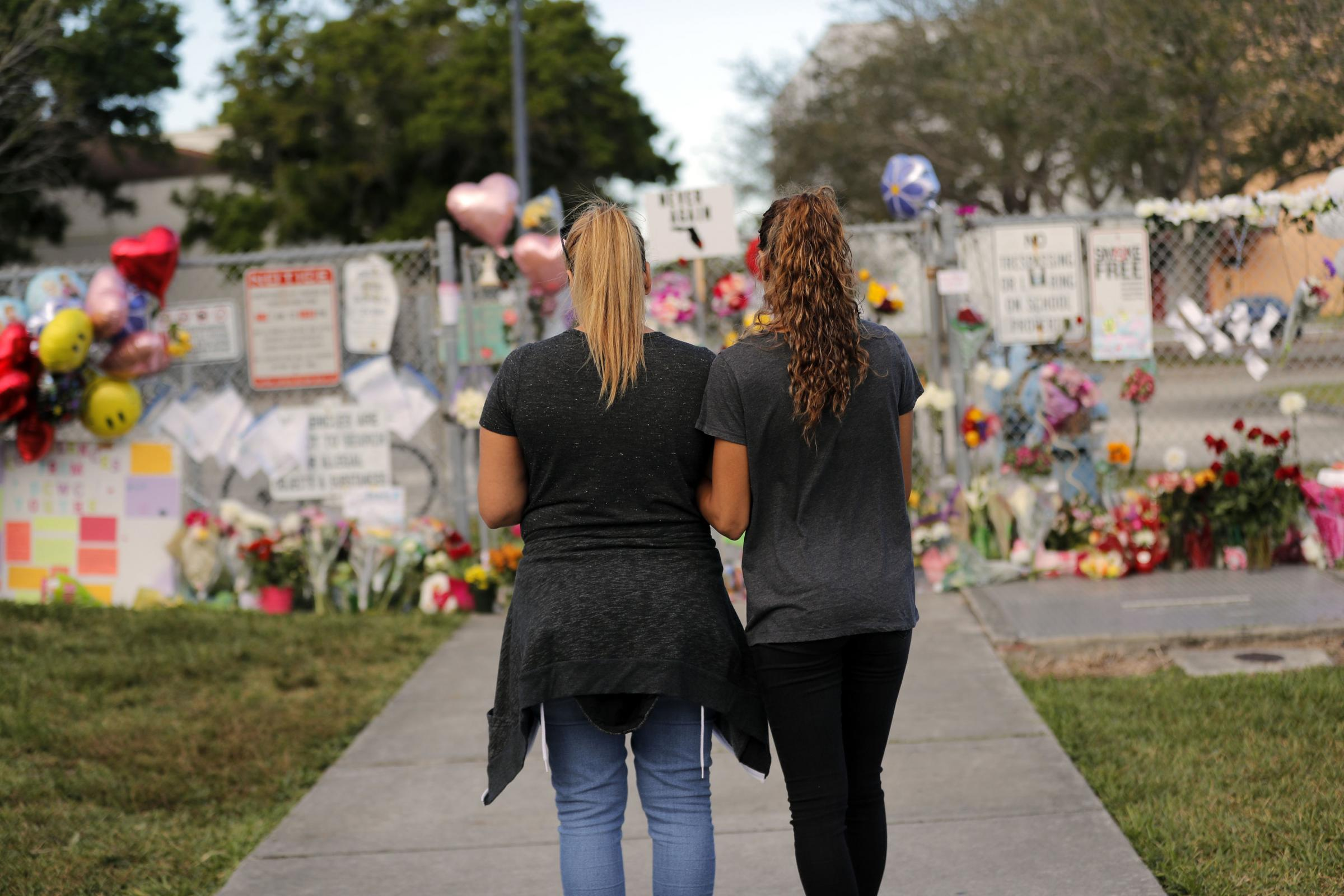 Sara Smith, left, and her daughter Karina Smith visit a makeshift memorial outside the Marjory Stoneman Douglas High School, where 17 students and faculty were killed in a mass shooting. Picture: AP