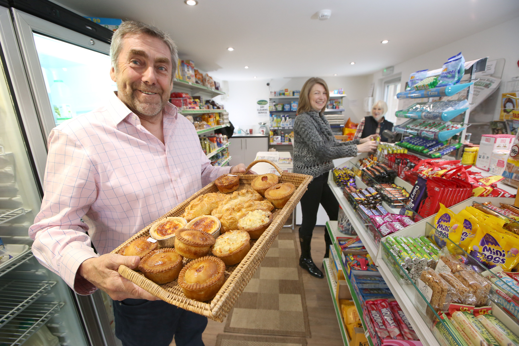 Cllr Stephen Watson is pictured with shop volunteers Patricia Watson (behind the counter) and Amanda Smith (stacking shelves).