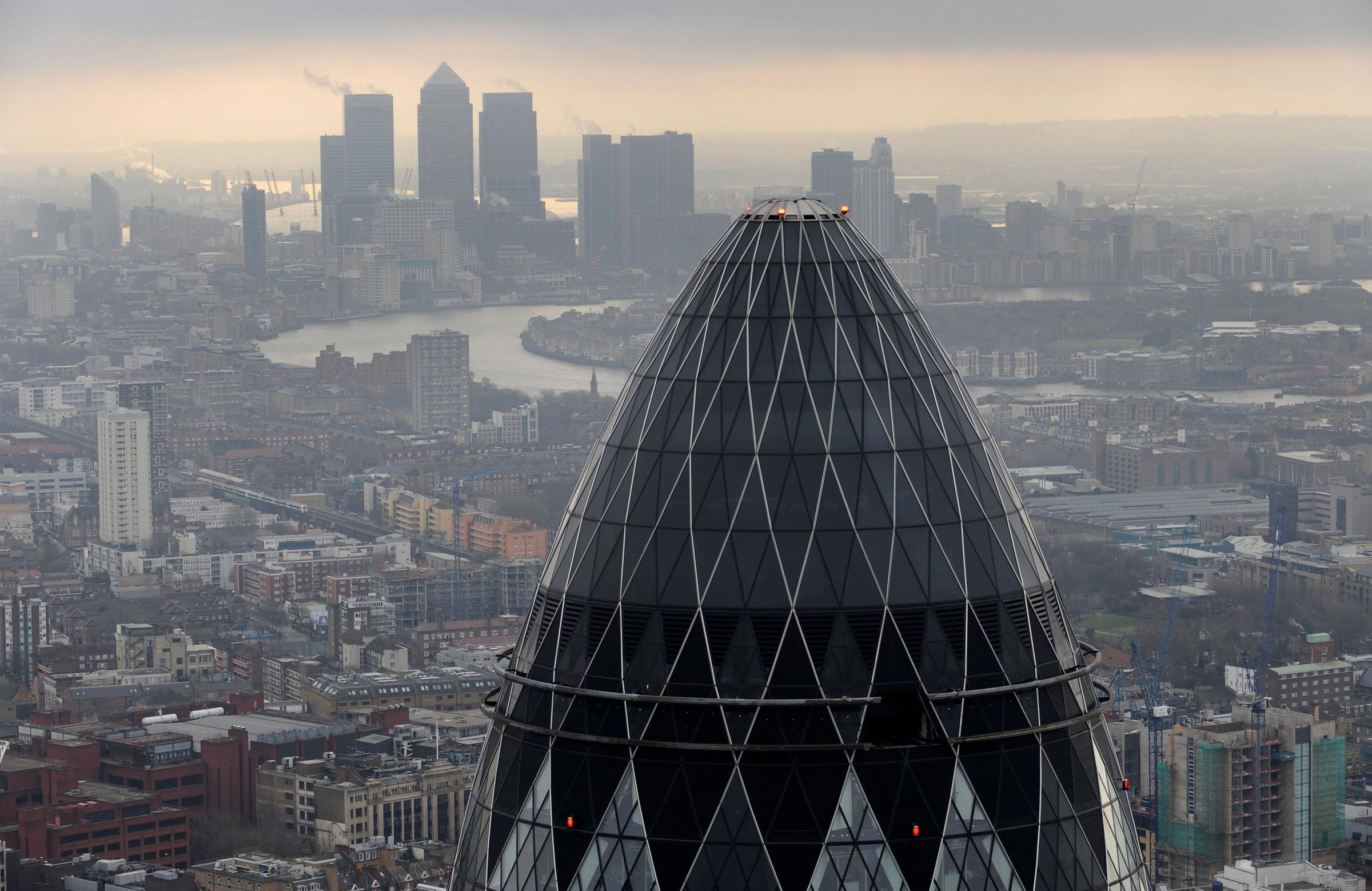 St Mary Axe also know as the 'Gherkin' and Canary Wharf at sunrise from the City of London. Picture: Stefan Rousseau/PA Wire