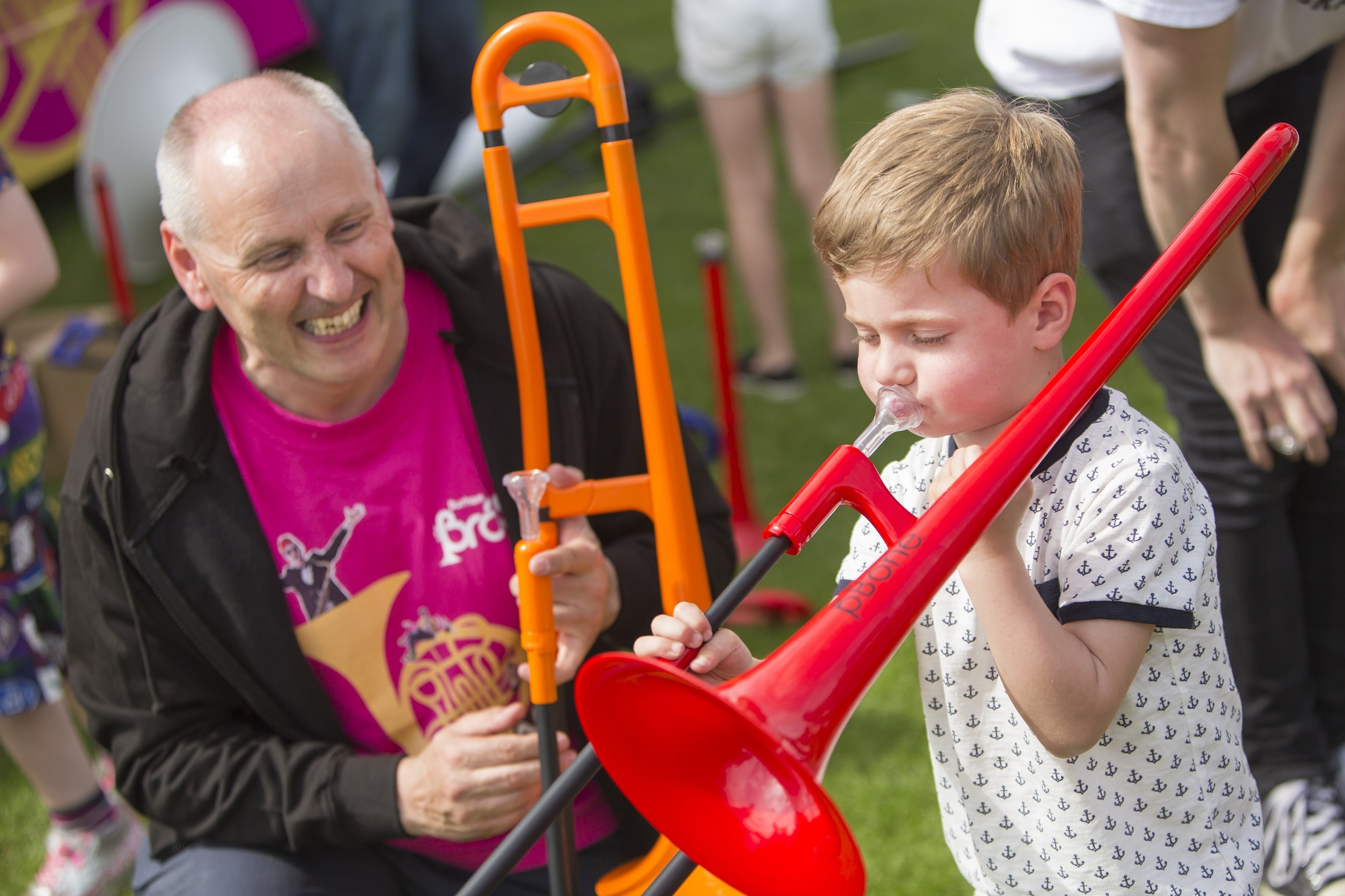 LEARNING: Paul Gudgin with Sebastian Fisher, five, from Chester-le-Street, playing a plastic trombone.