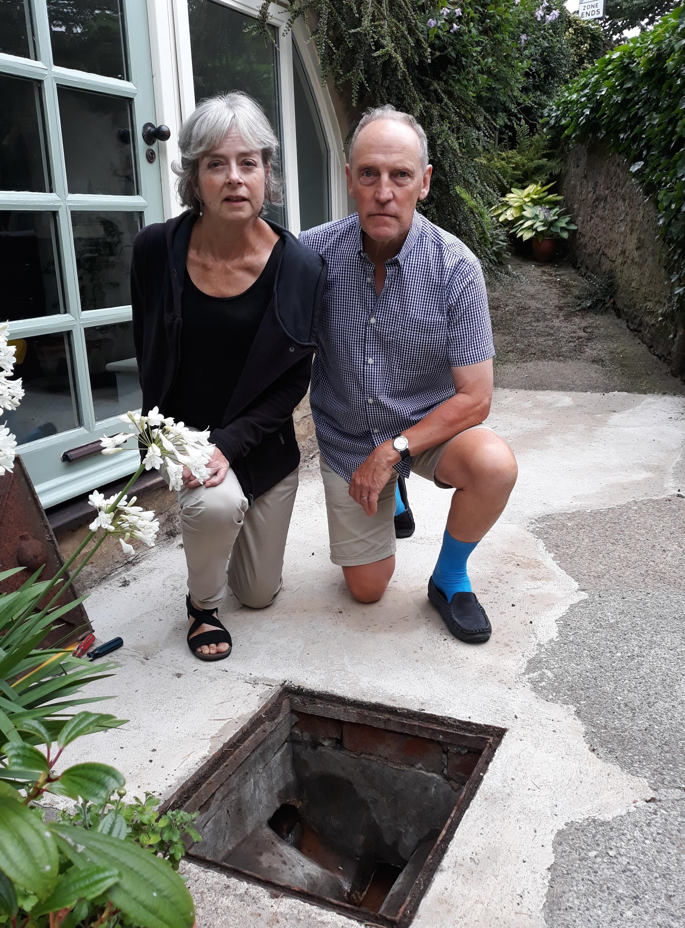 FRUSTRATION: Dave Dalton and Julie Martin next to the drain with water rushing through it