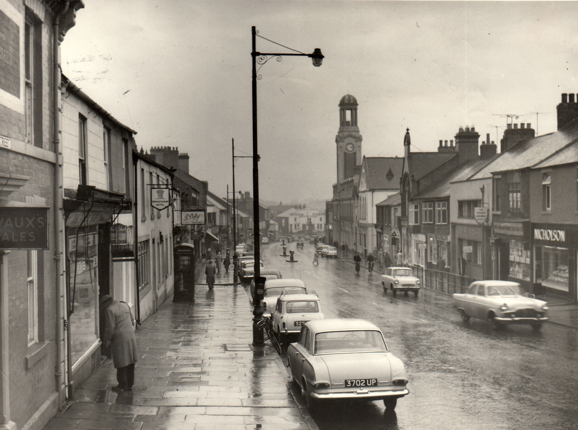OLD CAR PIC: Spennymoor High Street five days before Christmas 1963, and it was raining. On the left is the Wheatsheaf Hotel, which we think is now the Citizen's Advice Bureau, and on the right is The Vane Arms which last time we looked was Quinns Inn.