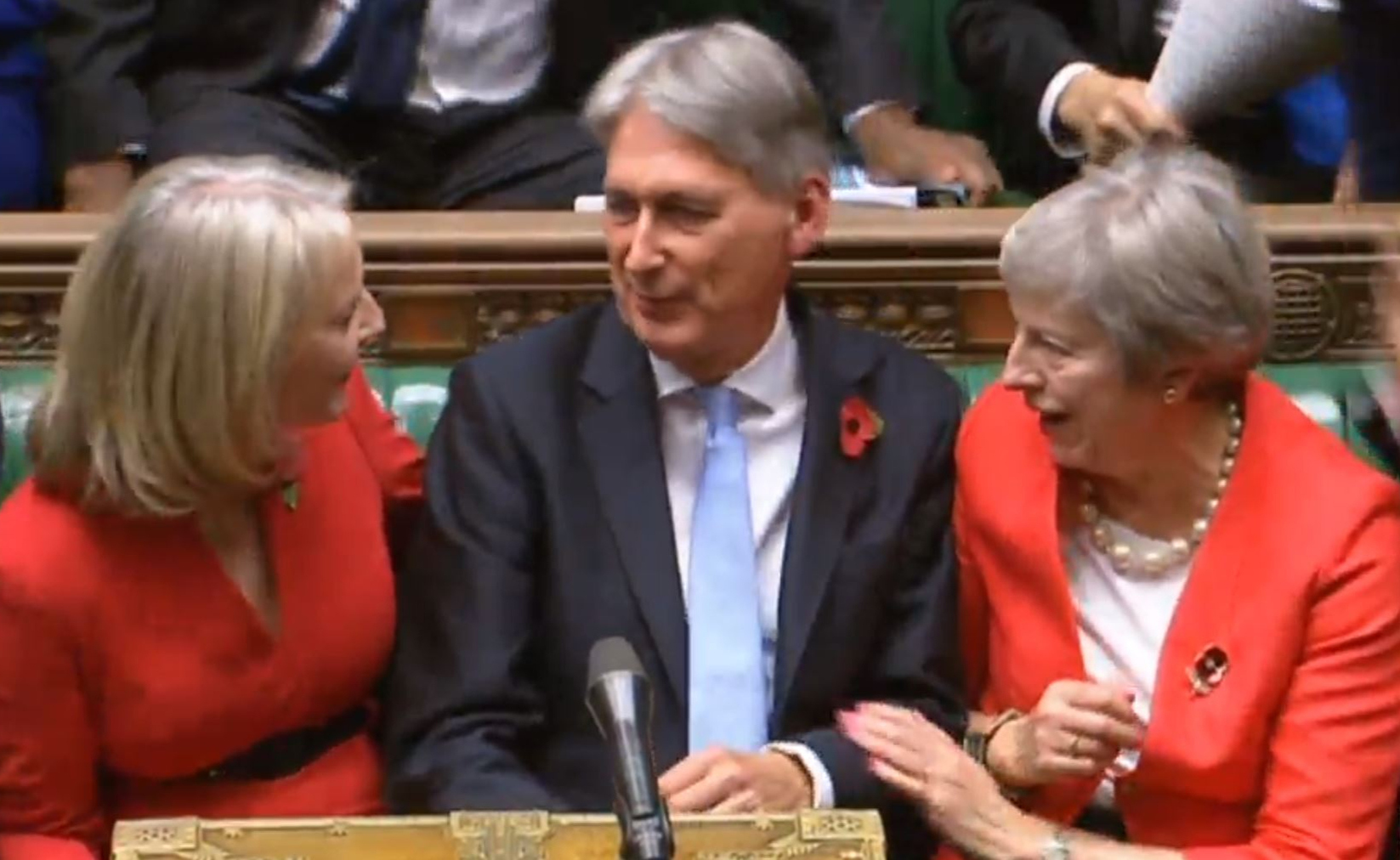 IN THE RED: Philip Hammond is congratulated by Treasury Chief Secretary Liz Truss and Prime Minister Theresa May, but he committed Britain to brrowing at least £20bn-a-year for the next five years