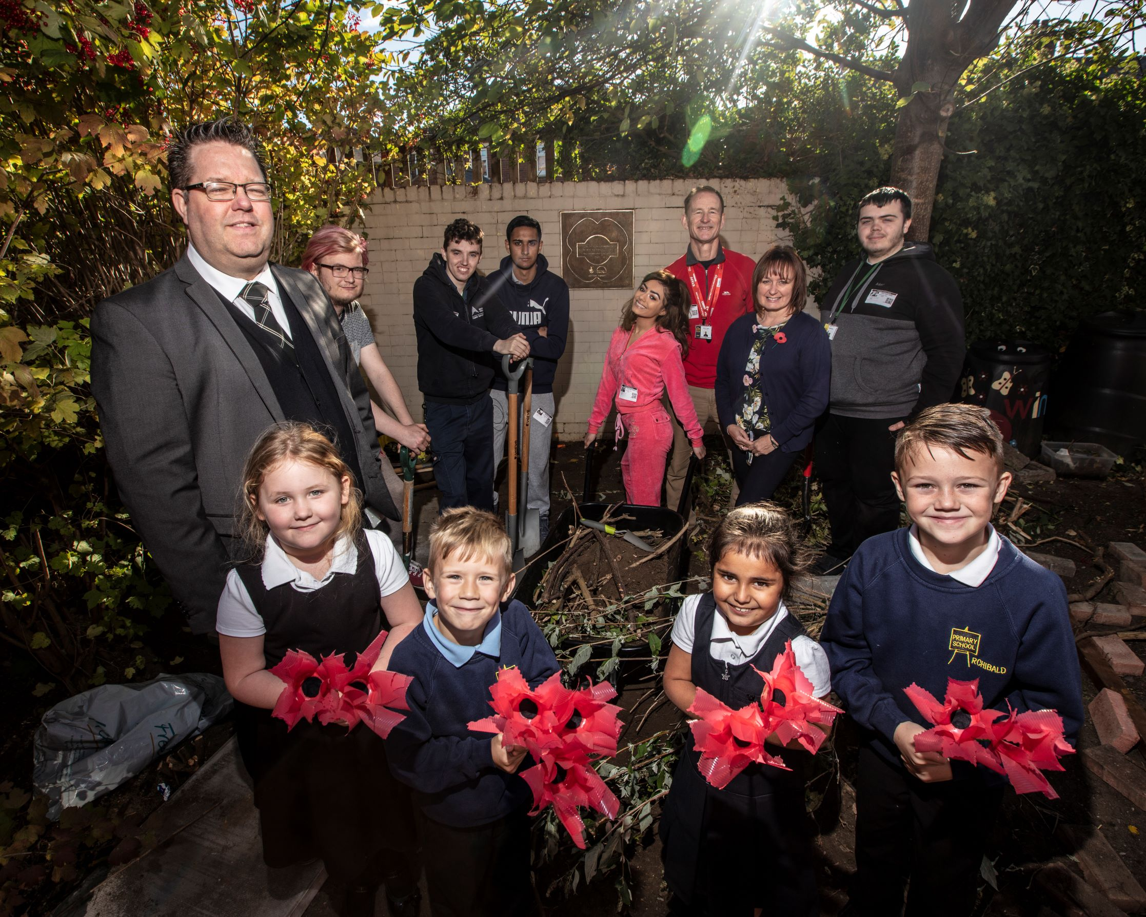 TRIBUTE: Clearing the way to the World War 1 remembrance plaque at Archibald Primary School. Front: Deputy Head Steve Cowgill with pupils and poppies they have made. Back: Diane Parker (second right) from funder UK Steel Enterprise and Team Leader Martin