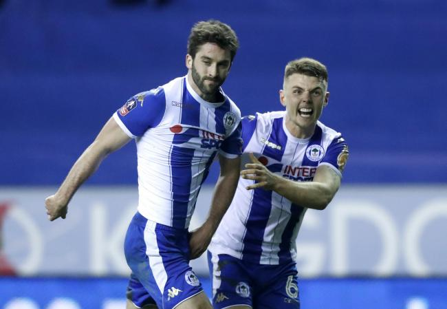 Wigan Athletic's Will Grigg (left) celebrates scoring his side's first goal of the game during the Emirates FA Cup, Fifth Round match at the DW Stadium, Wigan..