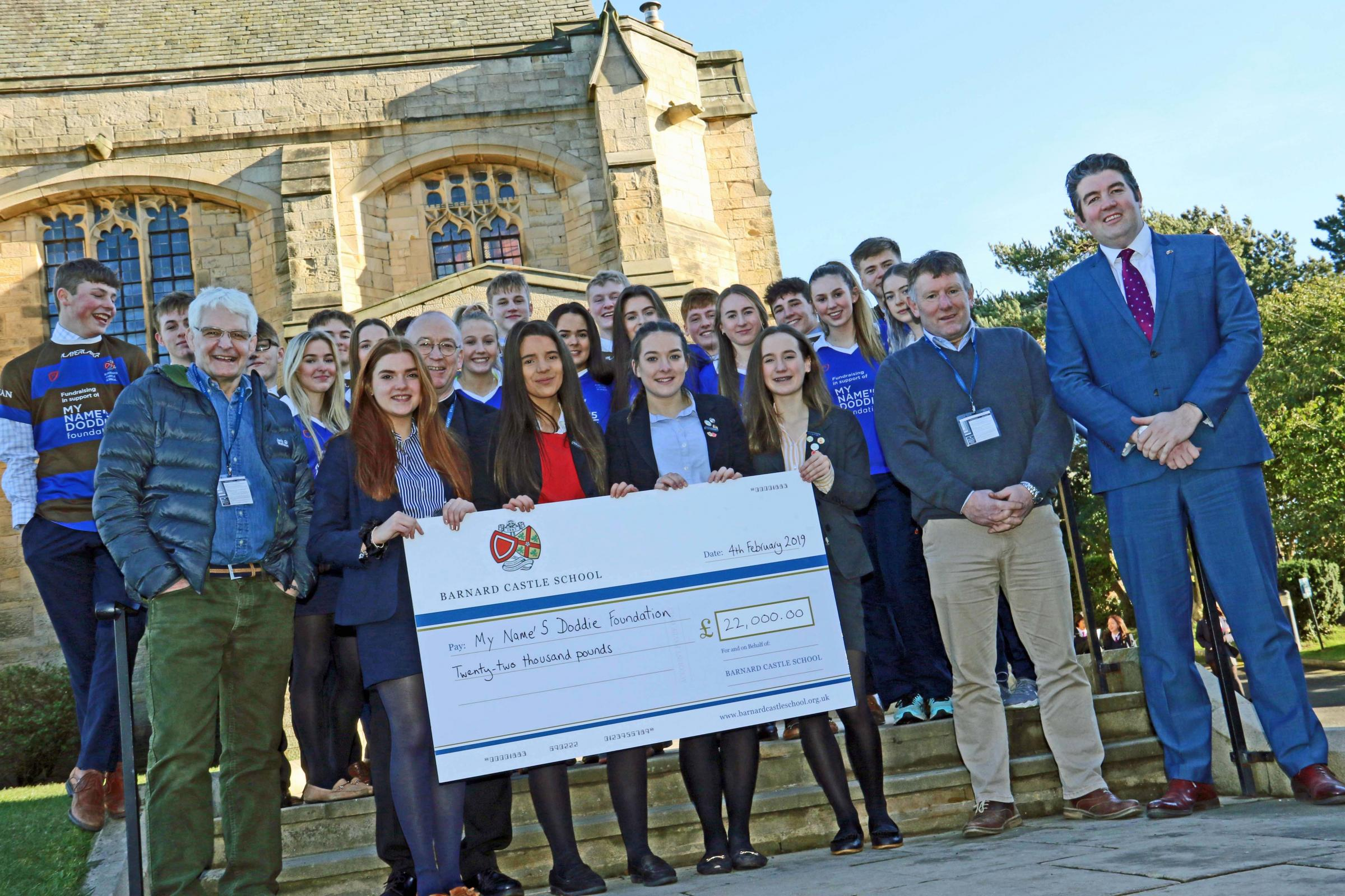 CHARITY MONEY: Barnard Castle School children and staff present a record-breaking cheque for £22,000 to the My Name'5 Doddie Foundation to fund research into motor neurone disease