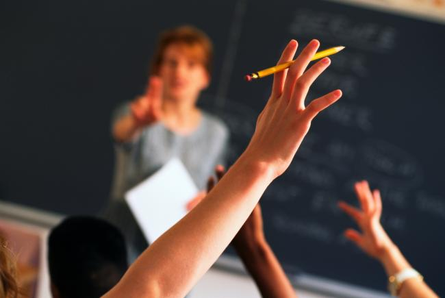 Teacher pointing to raised hands in classroom.