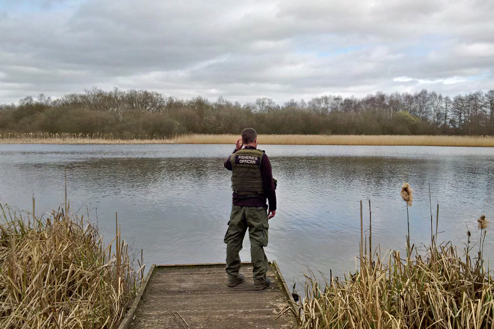 An enforcement officer looks out over a lake