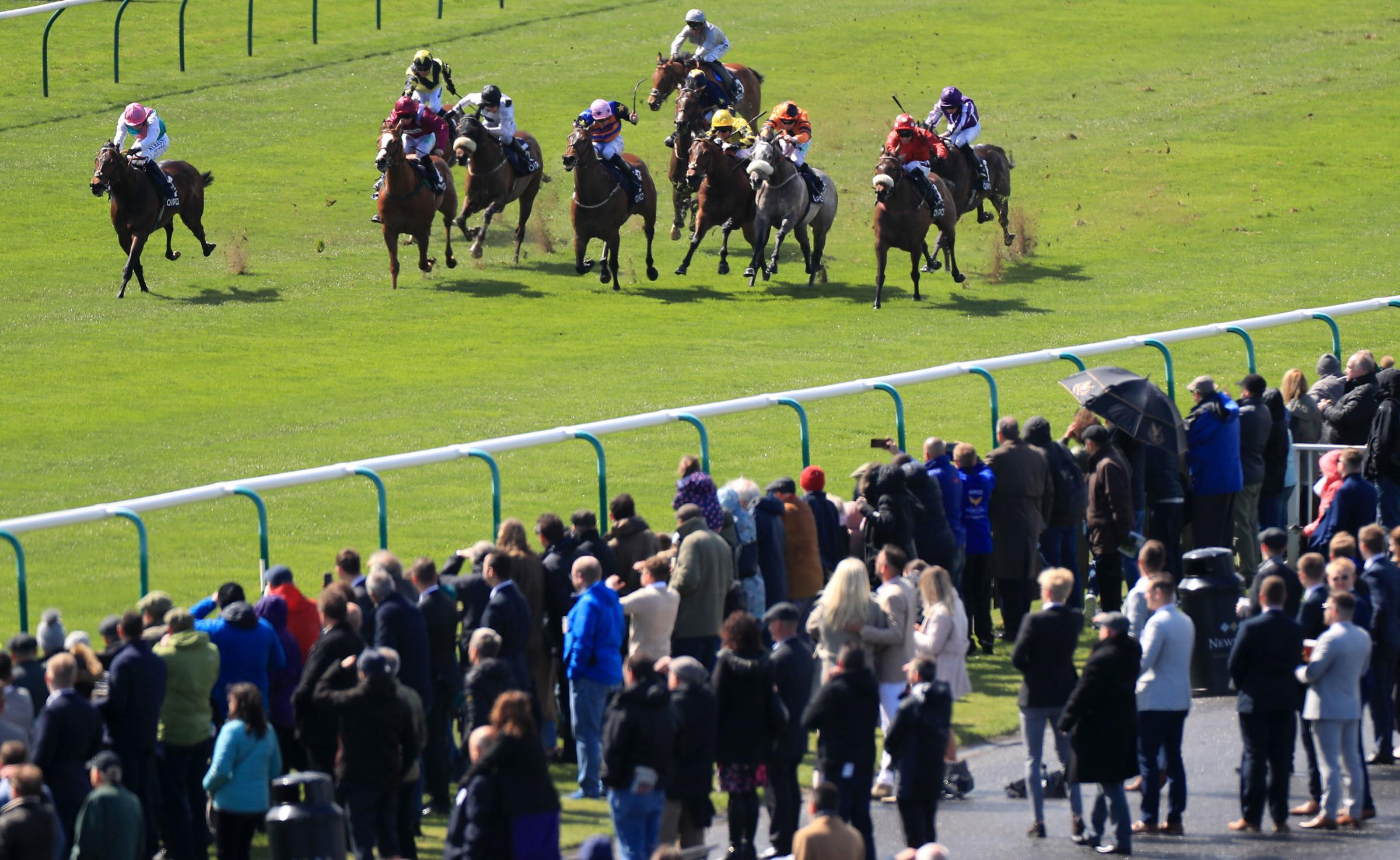 Racegoers watch the action as Mabs Cross ridden by jockey Paul Mulrennan (right) goes on to win the Zoustar Palace House Stakes ahead of Equilateral ridden by Oisin Murphy (left) at Newmarket last weekend. Picture: Mike Egerton/PA Wire